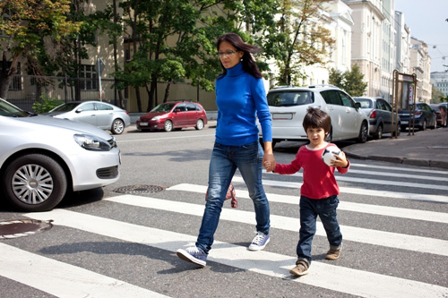 Mother and son are on a pedestrian crossing in the city